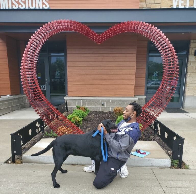 man crouched down with his large black dog in front of the KC Pet Project Heart Arch.