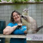 Danielle Bays wearing a blue shirt smiling at the camera. She has a cat next to her.