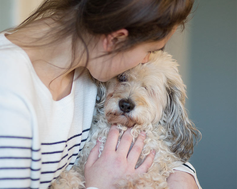 A woman holding her dog closely, kissing its face.