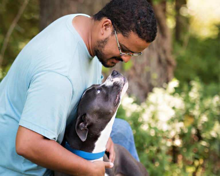 Black and white dog looking up at man wearing a blue shirt