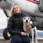 Kara Pollard with a dog in front of an airplane. Kara is wearing a black puffer jacket and jeans.