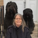 Kathy Duncan sitting on steps with two black fluffy dogs behind her.