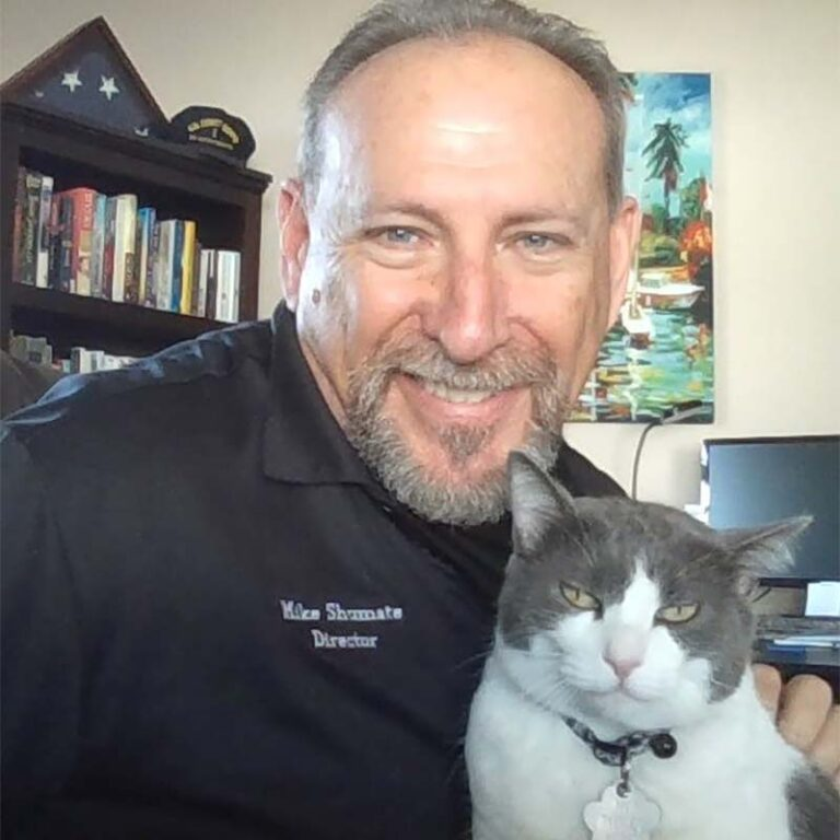 Michael Shumate with a grey and white cat smiling at the camera