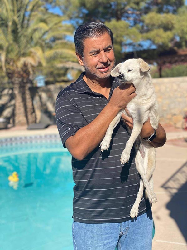 A man holding his small dog, Pancho, in front of a pool.