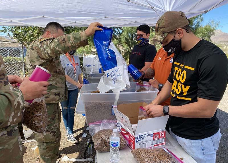 Volunteers filling bags of pet food.